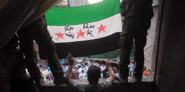 In this Friday, Sept. 21, 2012 file photo, Free Syrian Army rebels hold a revolutionary flag during a demonstration in the Bustan al-Qasr neighborhood of Aleppo, Syria.