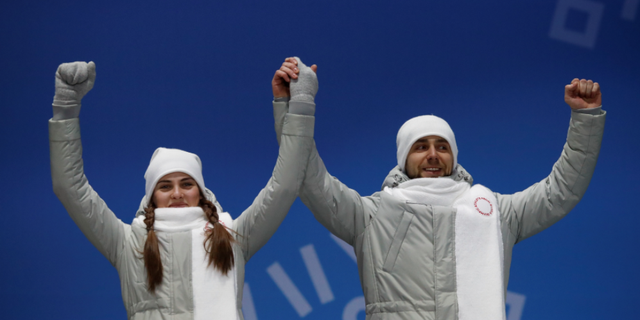 """Anastasia Bryzgalova and Alexander Krushelnitsky, """"Olympic Athletes from Russia,"""" on the podium at the 2018 Winter Olympic Games."""