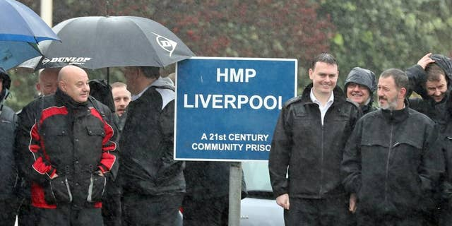 Prison officers stand outside Liverpool Prison as they strike over health and safety concerns, in Liverpool, England, Tuesday, Nov. 15, 2016. Britain's High Court has ordered thousands of prison officers to end a walkout over rising violence behind bars. embers of the Prison Officers Association protested Tuesday by stopping work, though they said they would respond to emergencies.( Peter Byrne/PA via AP)