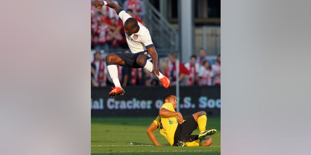U.S. forward Jozy Altidore, top, jumps to avoid Jamaica defender Adrian Mariappa during the first half of a World Cup qualifier soccer match at Sporting Park in Kansas City, Kan., Friday, Oct. 11, 2013. (AP Photo/Colin E. Braley)