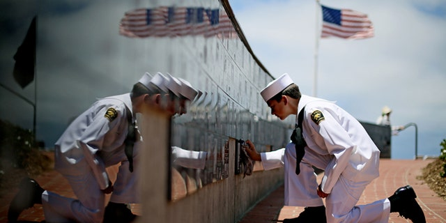Sea Cadet Andrew Culp, 13, cleans a war memorial during a Memorial Day ceremony at the Mount Soledad Veterans Memorial in La Jolla, Calif., May 27, 2013. (Associated Press)