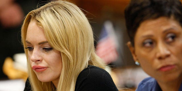July 6: Lindsay Lohan (left) sits in court with her lawyer Shawn Chapman Holley, before a judge sentenced her to 90 days in jail and 90 days in an in-patient rehab facility.