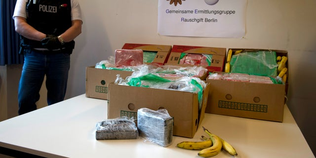 """A masked poliman stands next to banana crates with confiscated drugs in the police headquarters in Berlin, Tuesday Jan.7, 2014. Poster in center reads : Special Drug Investigation Group Berlin. Police say they have seized a large haul of cocaine after smugglers apparently made a mistake that saw the drugs end up in supermarkets. Workers at five stores in and around Berlin were surprised to find 140 kilograms (309 pounds) of cocaine packed into crates of bananas on Monday. The head of Berlin's anti-drugs squad said Tuesday that the crates had come from Colombia and the discovery was """"pure chance."""" German news agency dpa quoted Olaf Schremm as saying that the smugglers had probably made """"a logistical mistake."""" It's estimated that the drugs would have had a street value of about 6 million euro ($8.2 million).   (AP Photo/dpa, Daniel Naupold)"""