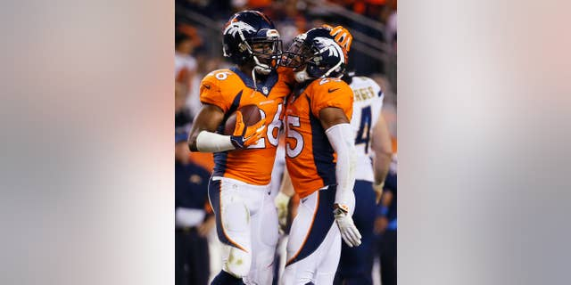 San Diego Chargers cornerback Brandon Flowers (26) celebrates his interception with teammate Chris Harris (25) during the second half of an NFL football game against the San Diego Chargers, Thursday, Oct. 23, 2014, in Denver. (AP Photo/Jack Dempsey)