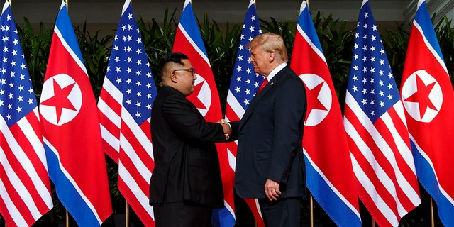 North Korean leader Kim Jong Un, left, and U.S. President Donald Trump shake hands prior to their meeting on Sentosa Island in Singapore Tuesday, June 12, 2018.
