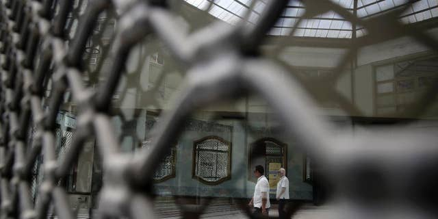 People are reflected on the glass of a shuttered shop as they walk in a shopping arcade, in central Athens, on Monday, May 25, 2015.  Greece's radical left-led government has ruled out restricting access to bank accounts and the free movement of capital if there is no breakthrough soon in tortuous negotiations with bailout creditors and the country runs out of money. (AP Photo/Petros Giannakouris)