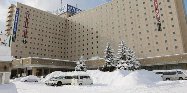 Snow-covered vehicles are parked in front of APA Hotel in Sapporo, northern Japan, Tuesday, Jan. 31, 2017.  Japanese organizers for next month's Asian Winter Games say nationalistic history books will be removed from guestrooms at the hotel that will be used to house athletes. The organizers also say Chinese athletes will stay at another hotel in accordance with a request from Beijing. (Kentaro Watanabe/Kyodo News via AP)
