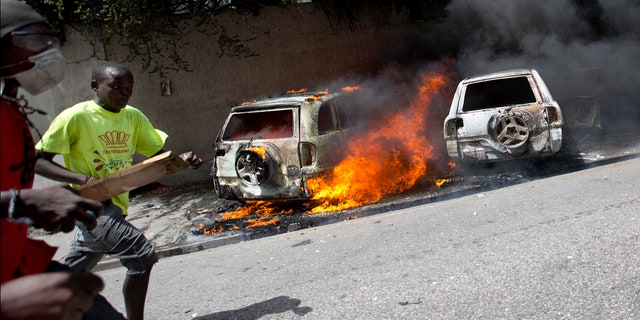 People run after cars were set on fire near the Best Western hotel during protests over a fuel price increase in Port-au-Prince, Haiti, on Saturday, July 7, 2018.