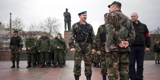 Members of the Crimean self defense forces gather for their morning briefing prior to patrolling the city at Soviet Union founder Vladimir Lenin's statue in Simferopol, Crimea, early Thursday, March 27, 2014. Crimea's government has decided to disband self-defense forces which provided help to the Russian military which have been occupying since late February. (AP Photo/Pavel Golovkin)