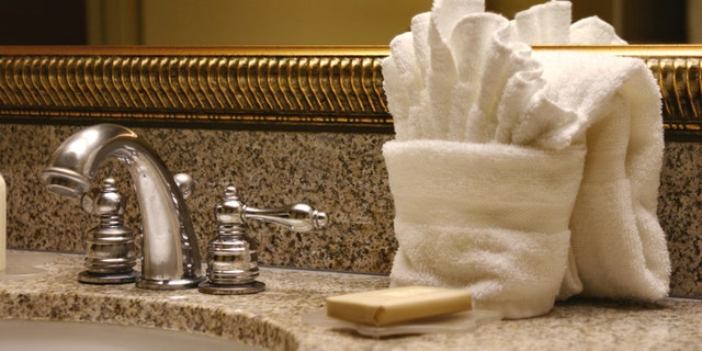 Hotel sink with soap and folded washcloth, towel, and mirror. Horizontal image.