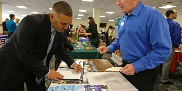 In this Friday, Feb. 6, 2015 photo, U.S. Marine Corps veteran Ignacio Yanes, left, writes information given by Jim Brooks, right, of the Small Business Administration at the annual Veterans Career and Resource Fair in Miami. The Labor Department issues its December report on job openings and labor turnover on Tuesday, Feb. 10, 2015. (AP Photo/Alan Diaz)