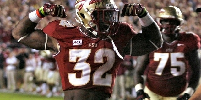 Florida State running back James Wilder Jr. (32) celebrates after scoring a touchdown against Miami during the second quarter of an NCAA college football game Saturday, Nov. 2, 2013, in Tallahassee, Fla. At right is offensive linesman Cameron Erving (75). (AP Photo/Phil Sears)