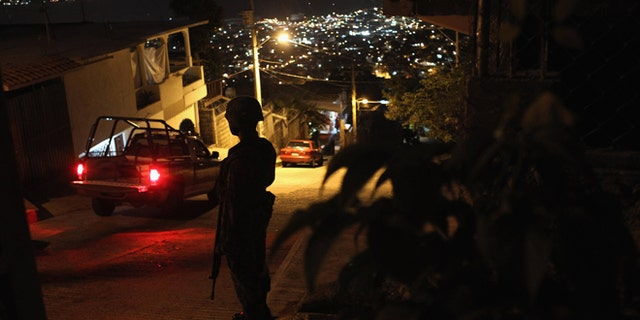ACAPULCO, MEXICO - MARCH 03:  A Mexican army soldier stands guard at a suspected drug-related murder site  March 3, 2012 in Acapulco, Mexico. A forensics team excavated five corpses from the floor of an abandoned house. Officials said the five victims were apparently buried alive in concrete. Drug violence has surged in the coastal resort in the last year, making Acapulco the second most deadly city in Mexico after Juarez. One of Mexico's top tourist destinations, Acapulco has suffered a drop in business, especially from foreign tourists, due to the violence. Toursim accounts for about 70 percent of the economy of Acapulco's state of Guerrero and 9 percent of Mexico's economy.  (Photo by John Moore/Getty Images)