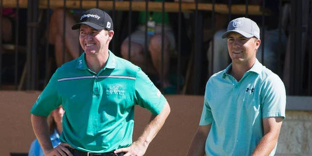 Jimmy Walker, left, and Jordan Spieth talk on the 16th tee during the final round of the Valero Texas Open golf tournament, Sunday, March 29, 2015, in San Antonio. Walker won the tournament. (AP Photo/Darren Abate)