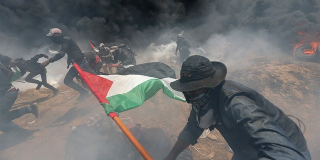 May 14, 2018: Palestinian demonstrators run for cover from Israeli fire and tear gas during a protest against the U.S. embassy move to Jerusalem.