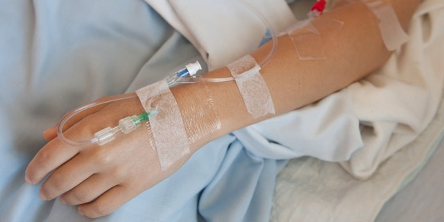 Woman in a hosptial with an IV drip in her hand and arm.