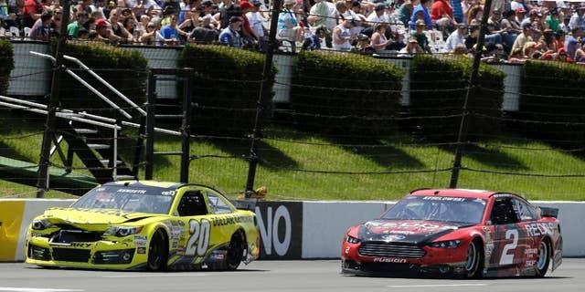 Driver Brad Keselowski (2) passes a damaged Matt Kenseth (20) during the NASCAR Sprint Cup series Pocono 400 auto race, Sunday, June 8, 2014, in Long Pond, Pa. (AP Photo/Mel Evans)