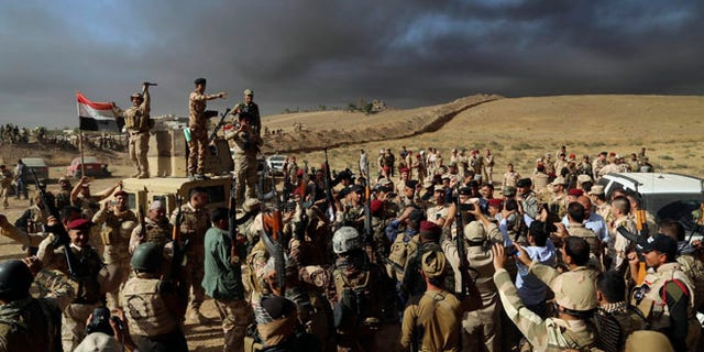 OCT. 21: Iraqi Army soldiers raise their weapons in celebration on the outskirts of Mosul, Iraq