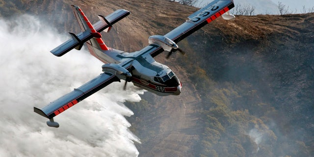 In this photo provided by the Santa Barbara County Fire Department, a Bombardier 415 Super Scooper makes a water drop on hot spots along the hillside east of Gibraltar Road in Santa Barbara, Calif., Sunday morning, Dec. 17, 2017.
