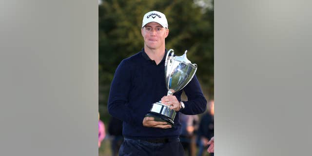 Sweden's Alex Noren celebrates with the trophy after winning The British Masters golf tournament at The Grove, Chandler's Cross, England, Sunday Oct. 16, 2016.  (Steven Paston / PA via AP)
