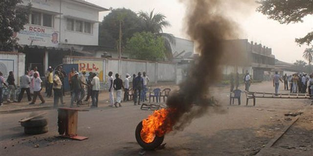 Opposition supporters burn tires and barricade a road in protest after armed men set ablaze an independent television station that the government had previously tried to silence, in Kinshasa, Congo, Tuesday, Sept. 6, 2011.