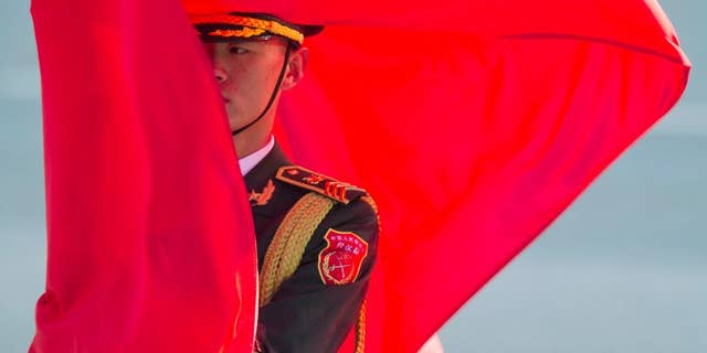 A member of a Chinese honor guard holds a flag before a welcome ceremony for German Chancellor Angela Merkel held outside the Great Hall of the People in Beijing, China, Thursday, Oct. 29, 2015 - file photo.