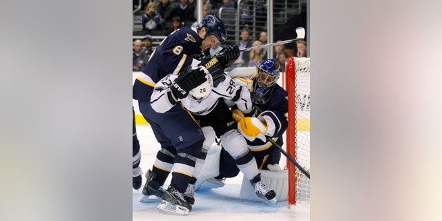 St. Louis Blues defenseman Kent Huskins, left, pushes Los Angeles Kings center Jarret Stoll in front of St. Louis Blues goalie Jaroslav Halak during the second period of an NHL hockey game in Los Angeles, Tuesday, Oct. 18, 2011. (AP Photo/Jae C. Hong)
