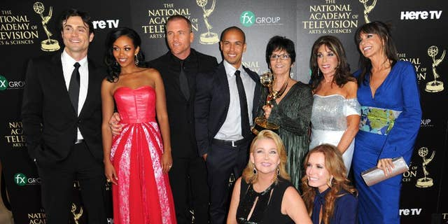 "The cast and crew of ""The Young and the Restless"" poses in the press room with the award for outstanding drama series at the 41st annual Daytime Emmy Awards in 2020."