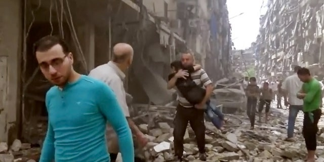 April 28, 2016 image made from video and posted online from Validated UGC, a man carries a child after airstrikes hit Aleppo, Syria.
