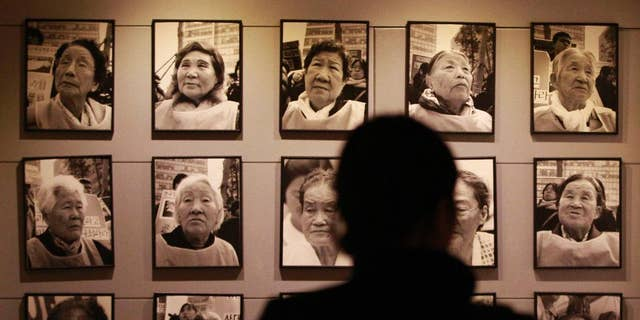 "FILE - In this Feb. 3. 2014, file photo, a visitor looks at portraits of late former ""comfort women"" who were forced to serve for the Japanese troops as a sexual slave during World War II, at the House of Sharing, a nursing home and museum for 10 former sex slaves, in Toechon, South Korea. 'Comfort women"" were present wherever the Japanese Imperial Army invaded and occupied in Asia from the early 1930s through the end of World War II. That aspect of wartime history was kept quiet until the early 1990s, when a South Korean woman came forward, joined by some others, seeking Japanese help and accountability. (AP Photo/Ahn Young-joon, File)"