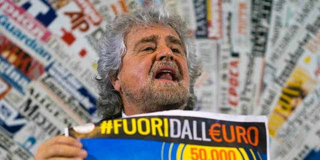"""FILE - In this Dec. 18, 2014 file photo, 5-Star Movement leader Beppe Grillo shows a poster in Italian reading """"Out of the euro, 50,000 signatures already collected in a weekend"""", as he speaks during a press conference at the Foreign Press Club in Rome. Italy's populist 5-Star Movement on Monday, Jan. 9, 2017 voted to join the liberal ALDE group in the European Parliament in an about-face power play that has sent shockwaves through the European Union legislature. (AP Photo/Domenico Stinellis, File)"""