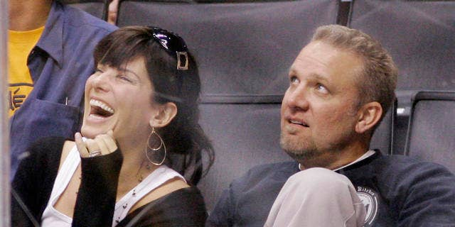 """**FILE** Actress Sandra Bullock laughs as she watches the video board with her husband Jesse James during the Los Angeles Kings' NHL hockey game against the Anaheim Ducks, in this Oct. 22, 2006 file photo in Los Angeles. Before she got to know him, Bullock says she tagged her husband as a brutish """"bigot."""" (AP Photo/Mark J. Terrill, file)"""