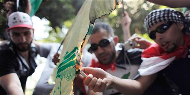 Protesters set fire to a Hezbollah flag, during an anti-Syrian regime rally near the Syrian embassy in Cairo, Egypt. Syrian troops fired Tuesday on residents who set up makeshift roadblocks to prevent the advance of tanks ringing the city of Hama, which has become a flashpoint of the uprising against autocratic President Bashar Assad, activists said.