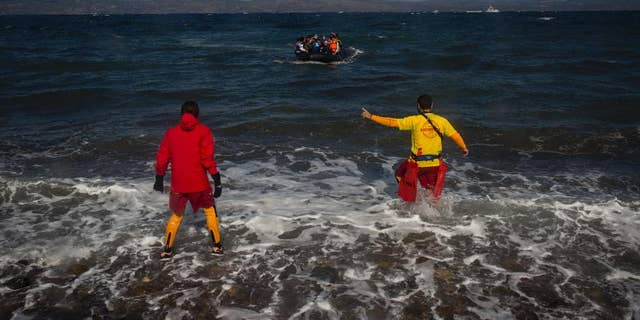 In this picture made on Wednesday, Oct. 28, 2015, members off Spanish rescue group Proactiva Open Arms wait to help an arriving dinghy carrying migrants to Lesbos island, Greece.   As this Greek island struggles with a huge migrant surge, a close-knit group of volunteers, many from overseas, work alongside Greek fishermen to rescue people at sea, provide medical care and bring comfort and basic necessities.(AP Photo/Santi Palacios)