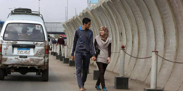 Egyptian couple walks past a concrete barrier surrounding the foreign ministry in Cairo, Egypt, Thursday, Nov. 27, 2014. Egypt's interior minister warned Tuesday that his forces will use deadly force to counter any assault against public facilities in a message coming just ahead of a planned protest by Islamists. (AP Photo/Amr Nabil)