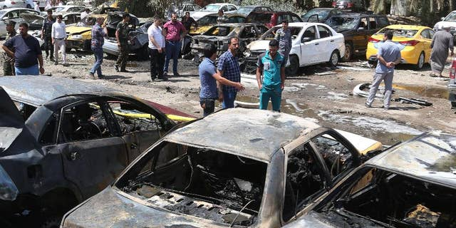 April 14, 2015: People and security forces gather at the scene of a car bomb explosion in a parking lot outside Yarmouk hospital in western Baghdad, Iraq. Car bombs went off Tuesday morning in and around the Iraqi capital, killing and wounding civilians, officials said.