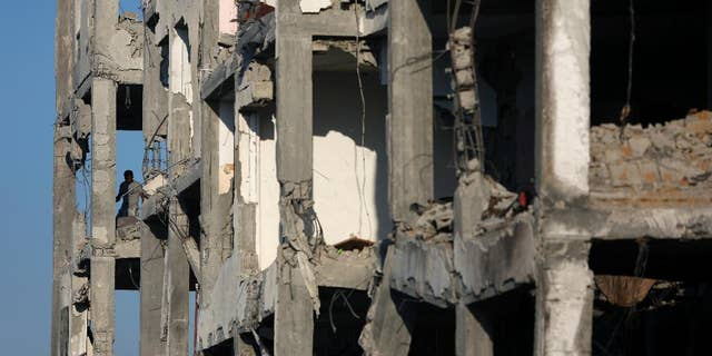 A Palestinian man inspects the damage of his flat in the destroyed Nada Towers residential neighborhood in the town of Beit Lahiya, northern Gaza Strip, Monday, Aug. 11, 2014.   A new temporary truce took hold, Monday, in the monthlong war pitting the Israeli military against rocket-firing Hamas militants as negotiators from Israel and the Hamas militant group resumed indirect talks in Egypt on Monday. (AP Photo/Khalil Hamra)
