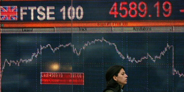 A woman walks past an electronic sign showing the progress of the FTSE 100 share index in London. London shares closed flat on Friday as a drop in resources stocks undermined the benchmark index, dealers said.