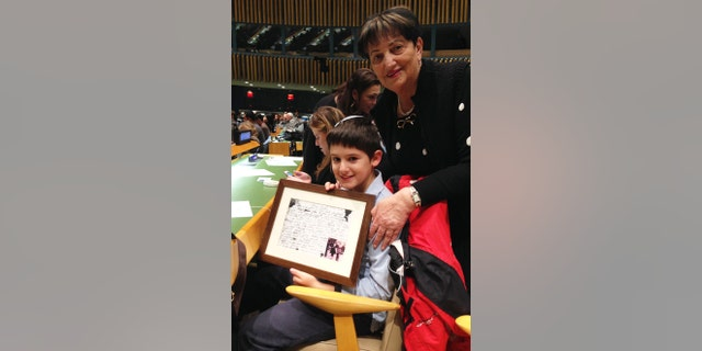 Amnon Schariawith his grandmother, Rita Scharia at the United Nations annual Holocaust Commemoration Ceremony in New York. Rita is a Holocaust survivor who traveled from Israel to be at the commemoration with her grandson and his family. Amnon is holding the last postcard she saved from her father who perished on the way to Auschwitz.