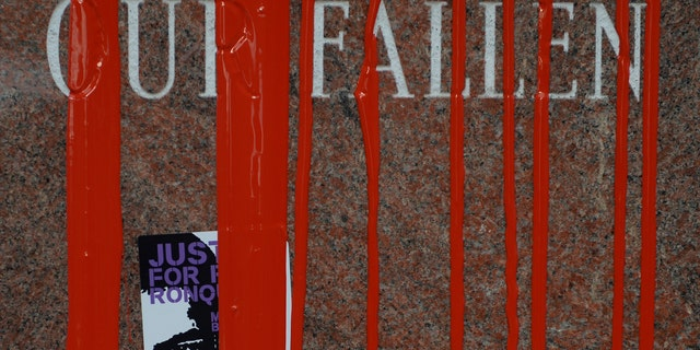 Stickers and red paint cover the fallen police memorial February 14, 2015 at the Denver Police Administration Building.