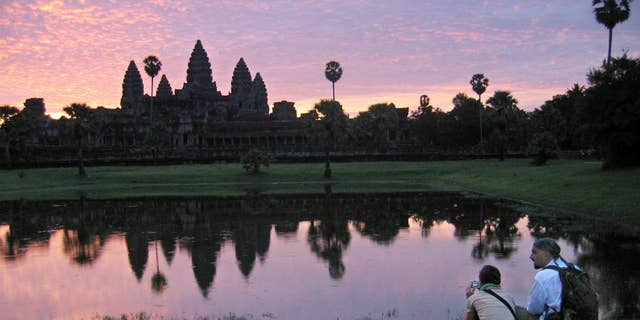 FILE - In this July 14, 2014 file photo, tourists look at the view of the Angkor Wat temples at sunrise, outside Siem Reap, Cambodia.