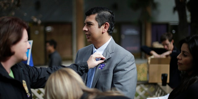 David Alvarez, center, a San Diego city councilman and Democratic candidate for mayor, stands while California Assembly Majority Leader Toni Atkins, left, adjusts a pin on his lapel as he meets with supporters Tuesday, Nov. 19, 2013, in San Diego. San Diegans head to the polls today to choose a new mayor, after Bob Filner's resignation amid allegations of sexual harassment has left the city with an interim mayor. (AP Photo/Gregory Bull)