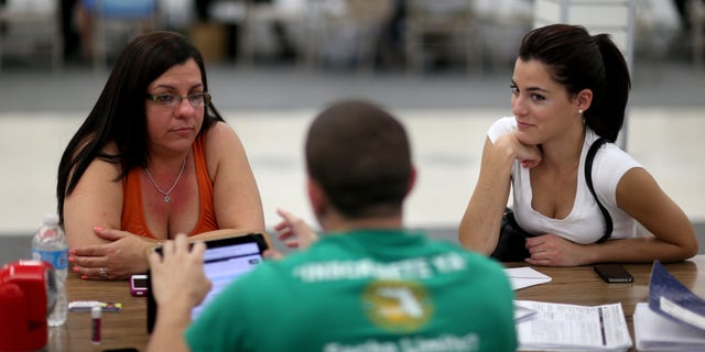 MIAMI, FL - MARCH 20:  Lidice Bacallao (L) andYislaine Diaz sit with Amaury Garcia an insurance agent from Sunshine Life and Health Advisors as they purchase individual health insurance policies under the Affordable Care Act at a store setup in the Mall of Americas on March 20, 2014 in Miami, Florida. The owner of Sunshine Life and Health Advisors, Odalys Arevalo, said she has seen a surge in people, some waiting  up to 3 hours or more in line, trying to sign up for the Affordable Care Act before the open enrollment period for individual insurance ends on March 31.  (Photo by Joe Raedle/Getty Images)