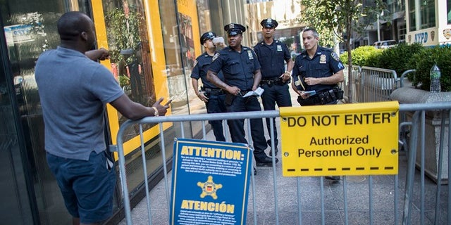 In this Thursday, Aug. 10, 2017 photo, police officers give a pedestrian directions while standing guard outside Trump Tower in New York.  Donald Trump plans to come home to Trump Tower for a few days starting Sunday, the first time since his inauguration. New York City police are planning a slight security clampdown in the area around the skyscraper for the duration of his visit. (AP Photo/Mary Altaffer)
