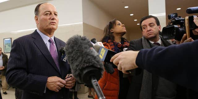 Stephen C, Worth, left, attorney for New York City police officer Peter Liang, speaks to reporters after Liang's arraignment at Brooklyn Superior court,  Wednesday, Feb. 11, 2015, in New York. Liang, who fired into a darkened stairwell last November at a Brooklyn public housing complex, accidentally killing 28-year-old Akai Gurley, has been charged with manslaughter, official misconduct and other charges. He was released without bail. (AP Photo/Mary Altaffer)