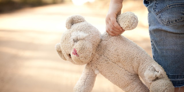 Color stock photo of a little runaway girl holding an old teddy bear at the side of a dirt road in the rural country.