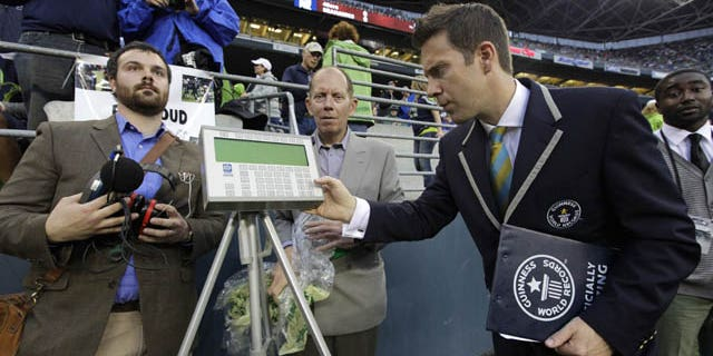 September 15, 2013: Philip Robertson, right, an adjudicator with Guinness World Records, examines a device used to measure the sound level of cheering fans at CenturyLink Field in Seattle prior to an NFL football game between the Seattle Seahawks and the San Francisco 49ers. (AP Photo)