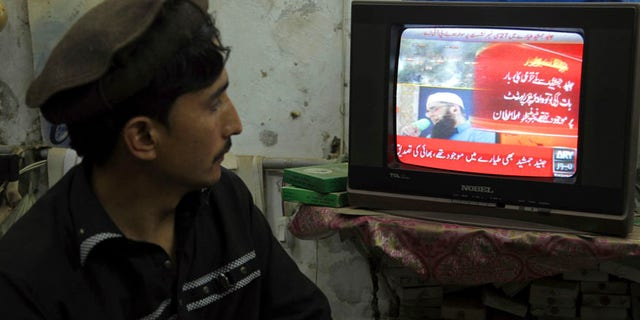 A Pakistani watches a local news channel broadcasting a report about a passenger plane taking off from Chitral, in the country's north, that crashed near a village near the town of Havelian, at his shop in Lahore, Pakistan, Wednesday, Dec. 7, 2016. The plane belonging to Pakistan's national carrier crashed on Wednesday with about 42 passengers and five crew members and an engineer on board, apparently killing all of them, police and an airline spokesman said. (AP Photo/K.M. Chaudary)
