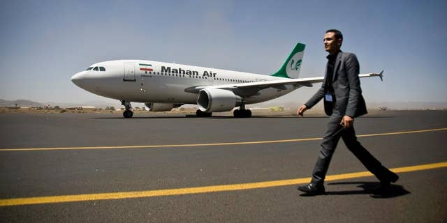 FILE -- A Yemeni airport security official walks on the tarmac next to a plane from the Iranian private airline Mahan Air at the international airport in Sanaa, Yemen, Sunday, March 1, 2015.