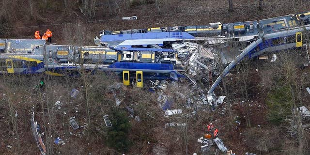 FILE - In this Feb. 9, 2016 file photo rescue teams work at the site where two trains collided head-on near Bad Aibling, Germany, killing twelve people and injuring 89. On Monday, Dec. 5, 2016 the train dispatcher was sentenced to 3 years and six months in prison because of negligence that led to one of the worst train crashes in German history this year.  (AP Photo/Matthias Schrader, file)